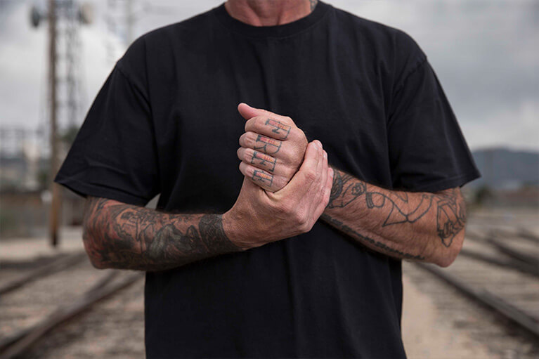 Tattooed man rubbing hands together